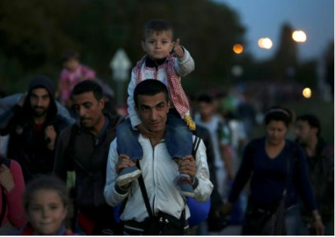 A refugee carries a child as he makes his way through the border from Hungary towards the Austrain town of Nickelsdorf September 21 Photo credit Reuters/DAVID W CERNY